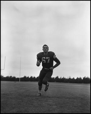 Primary view of object titled '[Football Player No. 67 Running on a Field, September 1962]'.