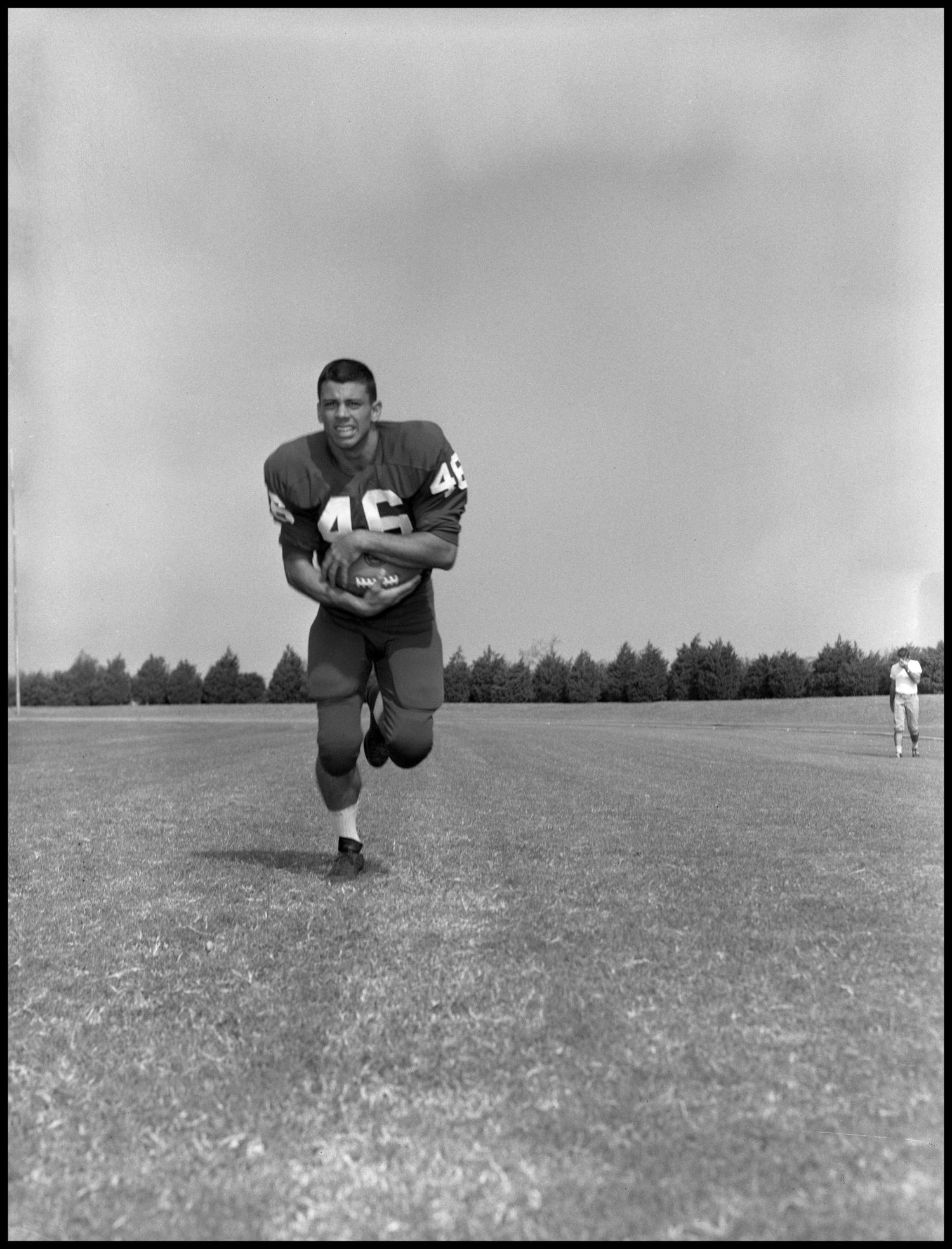 [Photograph of Bobby Richardson], Photograph of Bobby Richardson, a football player at North Texas State College. He holds a football and wears jersey number 46. Another man can be seen in the right of the image.,