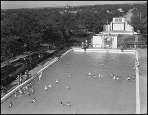 Black and white photo of a large pool with only a few people swimming in it. Beyond the pool is an expanse of trees.