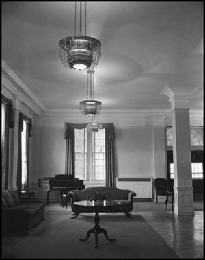 Black and white photo of an open room with two couches, a small round table in the middle of it. There are three windows that have drapes. A chandelier is in the middle of the room.