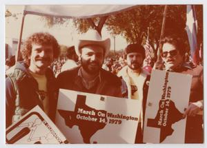 4 men stand side by side each other holding March on Washington signs. Second man from the left wears a cowboy hat, farthest man on the right wears sunglasses.