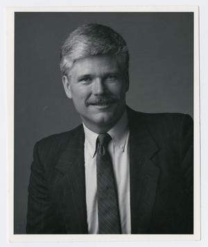 Black and white portrait of a man in a black suiit and tie, and white shirt under. He has a mustache.