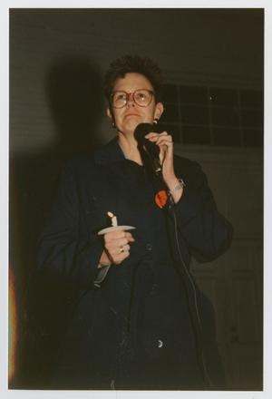 Woman with short cropped hair and thin red glasses stands with a microphone held in her left hand, with it close to her mouth. In her right hand is a lit candle. She wears a long blue coat with an orange button it.
