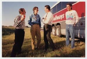4 men stand on the grass by the side of a Railways bus. Man on the farthest left has a black and white striped shirt, with a Big Gulp cup in his right hand.