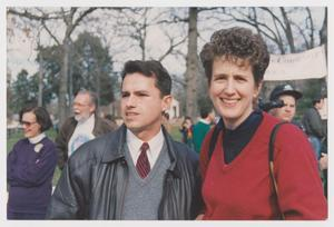 Man in black leather jacket stands next to a woman, with short hair, to his left. The woman wears a red sweater. Other people are seen behind them.