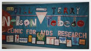 Blue banner with the names Bill Nelson and Terry Tobedo on it. A light pink upside down triangle is in the center of it, different patches with symbols are seen on it.