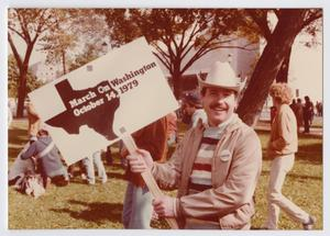 Man in a white cowboy hat holds a March On Washington sign with the date and black shape of Texas on it. People are seen on the grass behind him, by several trees.