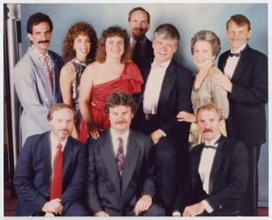 Portrait with 3 men sitting in the front, and 4 men and 3 women standing in the back. The men all have mustaches and suits, and all the women wear dresses.
