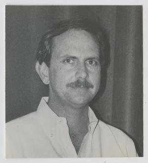 Black and white photo of a man with a mustache in a white collared shirt.