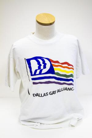 White t-shirt with pride flag on it and the words Dallas Gay Alliance on it.