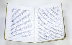 Open journal with white-lined pages. They are filled with neat cursive writing.