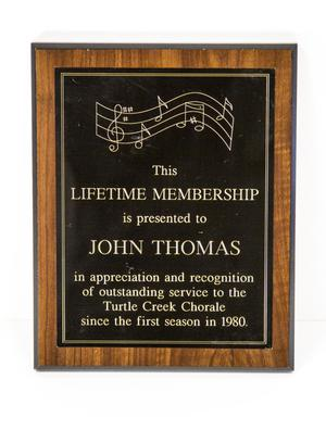 Rectangle shaped award. It is black, with wooden frame around it. Music notes line the top of it, with the words for the award on it.