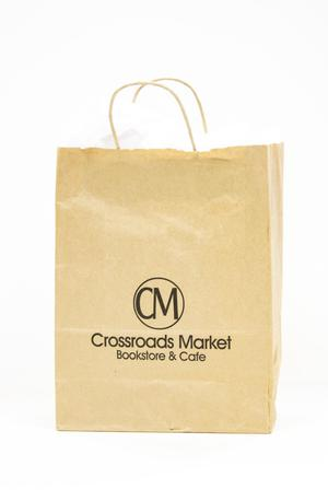 Light brown paper bag with small handles. The initials CM are on it inside a circle. The look of it is fairly simple.