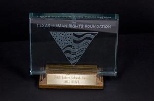 Clear award with the words Texas Human Rights Foundation on it. It stands on a wooden stand and golden plaque.