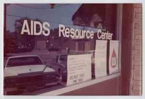 Window with the wors AIDS Resource Center on it in bold white letters. A reflection of 3 cars is seen in the window.