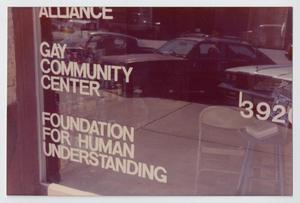 Window with the reflection of three cars on it. The words Gay Community Center are seen on it, a chair is seen inside.