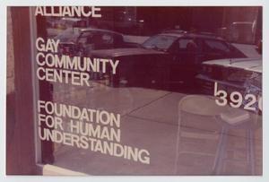 Ventana con el reflejo de tres autos. Pueden verse las palabras Centro Comunitario Gay y hay una silla en el interior.