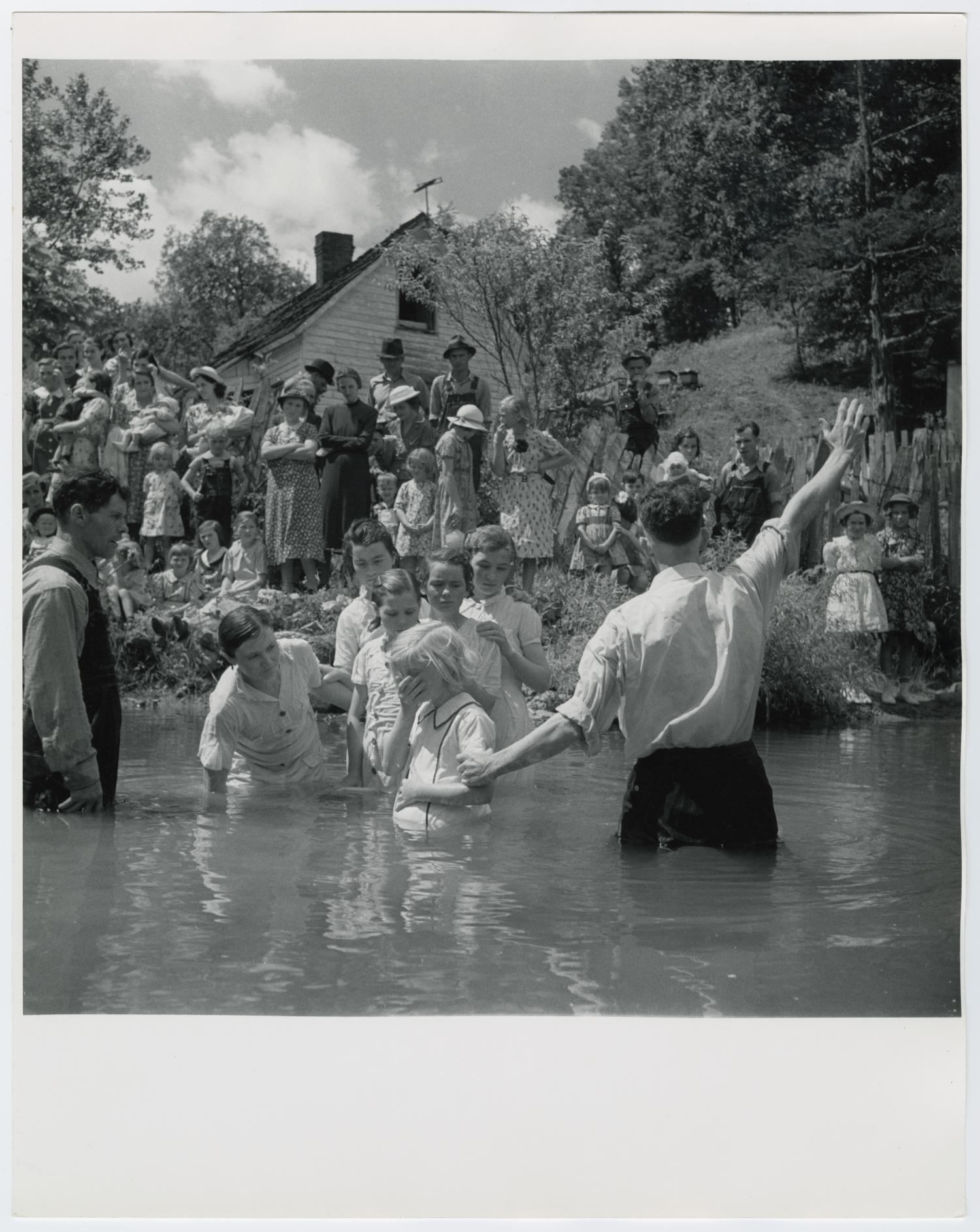 """Baptising in Olde Towne Creek, Narrative by Junebug Clark: Photograph is from 1938 and is shot in Red Hill, Tennessee. One of the first photos made by Joe, Baptising in Olde Towne Creek, has endured to become a favorite and meaningful to many. It bears close scrutiny because of the differing expressions and attitudes of those attending. People have said that they have counted fifty-one people in this picture and I've listened to many a controversy about a TV antenna* appearing in this 1938 photo. The Rev. Hugh Vancel, in charge in this photo, performed countless baptisms, but the ceremony eventually moved indoors. Olde Towne Creek empties into Keg Branch, a creek that runs though our property, about three miles left of your view point. To your right, about a mile, is the Clark family cemetery where Joe was laid to rest in December of 1989. In 1981 the Smithsonian Institute displayed a print of this photo for use in an exhibit """"Rights of Passage."""" It was published in the autobiography of Dolly Parton and as the poster for the Wolf Trap Music Festival. Jb. *lightning rod,"""
