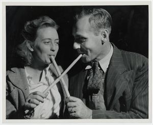 Primary view of object titled '[Couple Sampling the molasses with Sop Sticks]'.