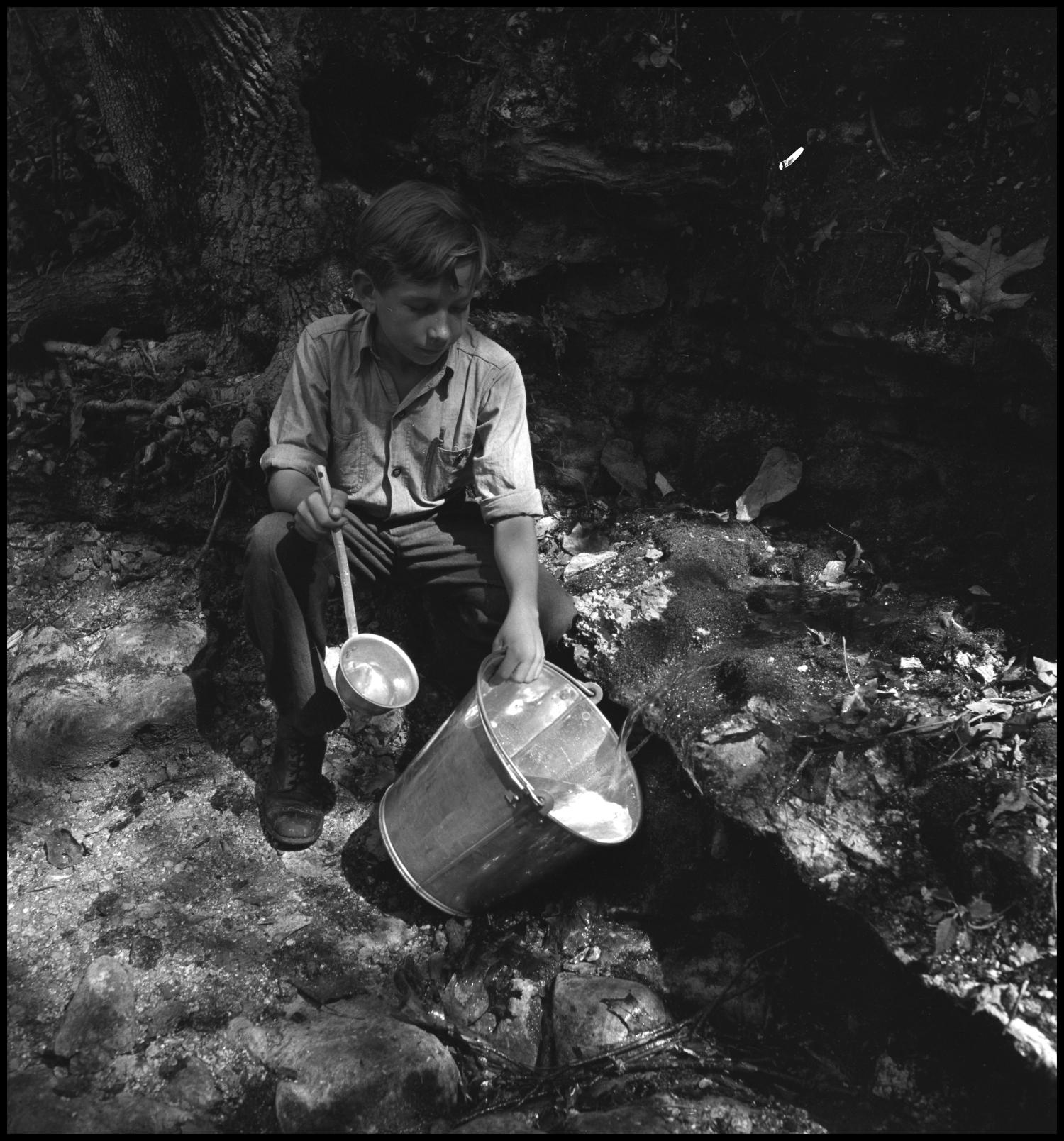 [Boy filling bucket from stream], Photograph of a boy kneeling alongside a stream as he fills a bucket with water. He holds a ladle in his right hand.,