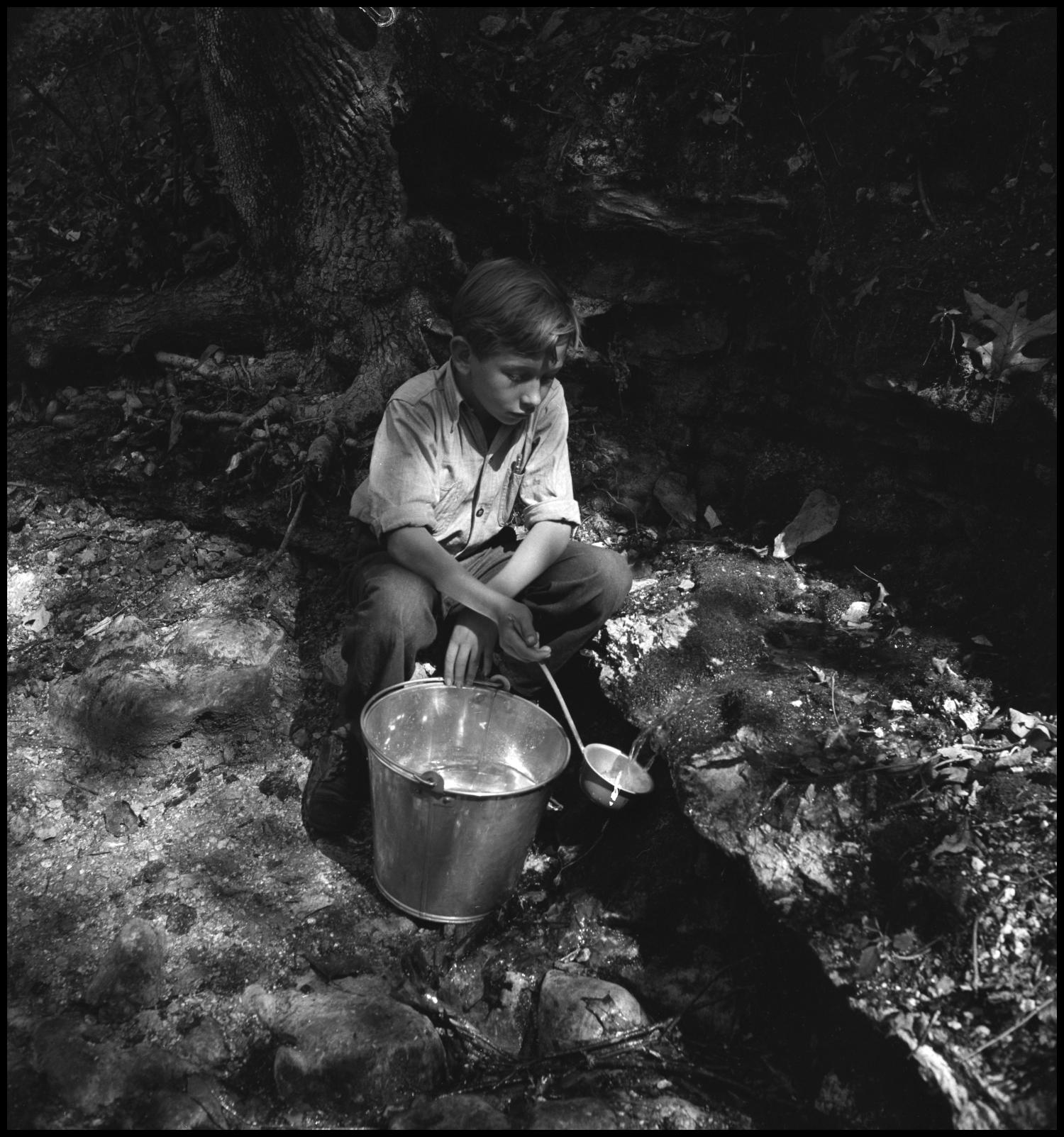 [Boy filling bucket from stream(1)], Photograph of a boy kneeling alongside a stream as he fills a bucket with water by using the ladle he holds in his right hand.,