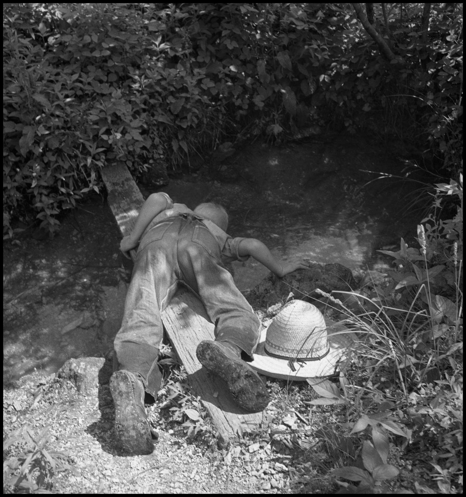 [Drinking Out of the Spring], Photograph of Roy McCrary getting a drink out of the spring at Vertical Acres. McCrary rests his hat on the ground as he leans across a plank of wood to reach the water.,