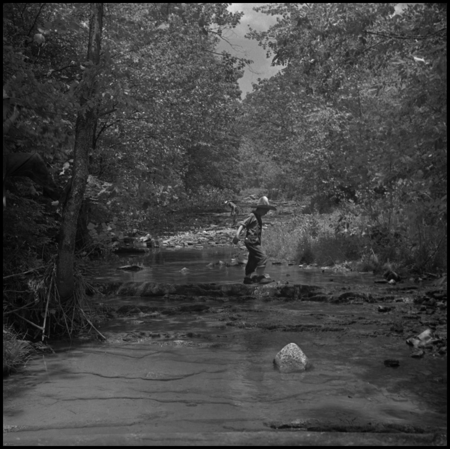 [Father and son walking the stream], Photograph of young Roy McCrary crossing a stream at Vertical Acres. From Junebug Clark: A father and son walking through the stream in the Hills of Tennessee, looking for lifes treasures. This is something Joe did with his siblings and his father after a days work. Peaceful and beautiful scene of a quiet stream to cool your feet and clear your mind.,