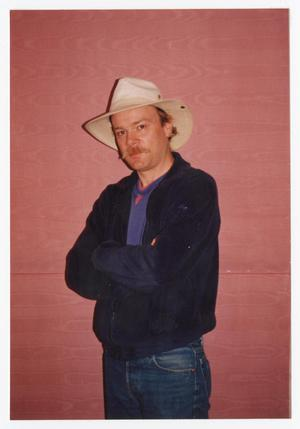Man in cowboy hat, wearing jeans and a dark blue jacket. He has a mustache, and is standing in front of a red wood wall.