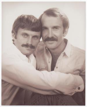 2 men, one with their arms around the other. Both have mustaches and are wearing white.