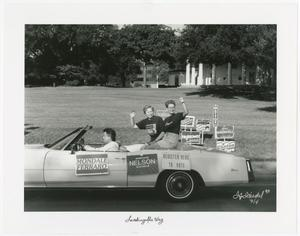 3 people sit inside a car with 3 posters on it saying Nelson, Register To Vote and more. A lawn of grass is behind them, with several signs close to where the car is.