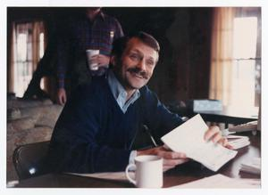 Man sitting at table with papers on it smiles to the side, in a sweater and with a mustache. White mug is on the table in front of him.