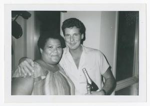 African American woman stands next to a man to her left. He has his arm around her with a bottle in his left hand and another one in his left arm.
