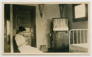 Primary view of object titled '[Irene Biffle Williams, reading in her dorm room]'.