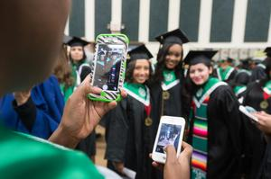 Primary view of object titled '[Students take photographs before UNT Commencement]'.