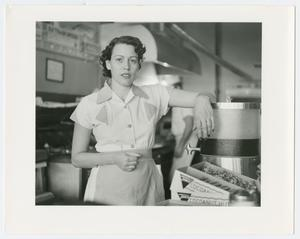 Black and white photo of a woman in a white waitress uniform, her arm propped up on a drink container.