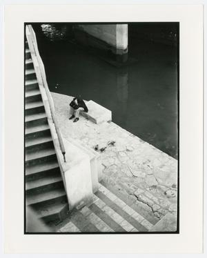 Seen from the top, a man is seen sitting on a bench by a river, a staircase on the left side.
