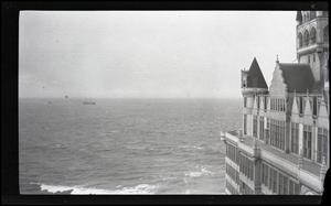 Black and white photo of several buildings. It is by a big body of water.