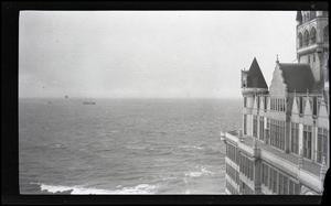 Foto en blanco y negro de varios edificios. Está junto a una gran masa de agua.