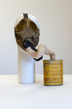 Gas mask attached to a white mannequin head. Attached to the tube is a yellow rusted can.