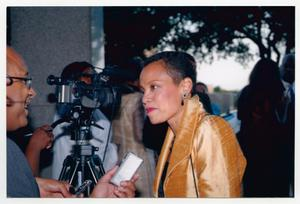 Primary view of object titled '[Harolyn Blackwell in Gold Coat Speaking to Interviewers]'.