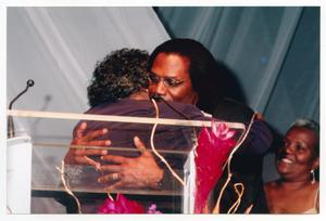 Primary view of object titled '[Curtis King Embracing Guest on Stage]'.