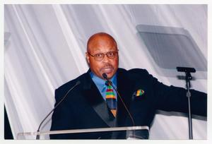 Primary view of object titled '[Roger E. Mosley Speaking on Stage]'.