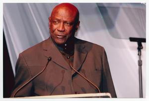 Primary view of object titled '[Louis Gossett Jr. Speaking at Podium]'.