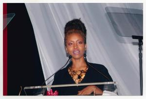 Primary view of object titled '[Erykah Badu Speaking at Podium on Stage]'.