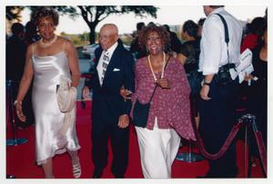 Primary view of object titled '[Three Guests Walking Down Red Carpet Together]'.