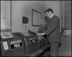 Primary view of object titled '[WBAP-TV Employee Reading a Message From a Teleprinter]'.