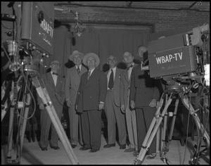 6 men in suits stand side by side behind two television cameras pointed towards them. Two of the men wear hats.