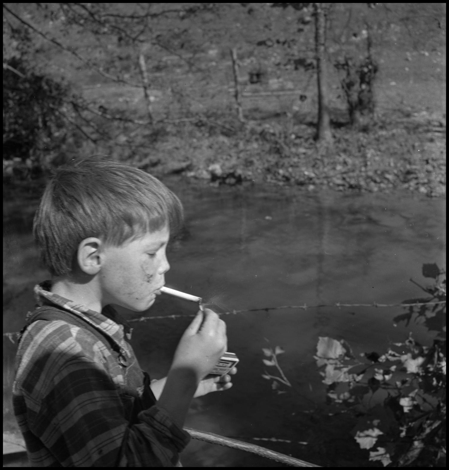 [Smoking boy], Photograph of a young boy lighting a cigarette. In the image, the unidentified boy, wearing overalls, is lighting his cigarette next to a stream separated by barbed wire.,