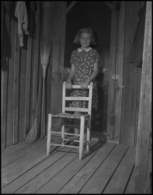 Primary view of object titled '[Girl standing behind a chair]'.