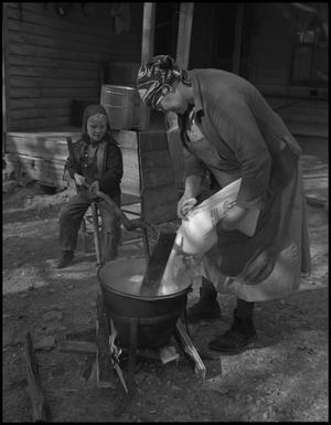 Primary view of object titled '[Pouring sugar into the apple butter]'.